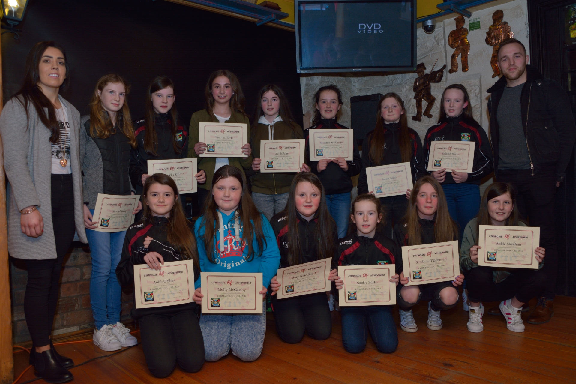 Cromane Under 12 Girls being presented with their certificates of achievement by Kerry Senior Players Sarah Houlihan & Darran O'Sullivan